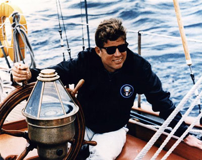 "President Kennedy at the helm of the U. S. Coast Guard yawl ""Manitou"". This was one of his favorite sailing yachts, and there are many White House Diary entries that describe cruising aboard ""Manitou"" with family and friends."